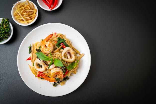 揚げたスパイシーな麺とシーフード (pad cha talay) をかき混ぜるタイ料理のスタイル