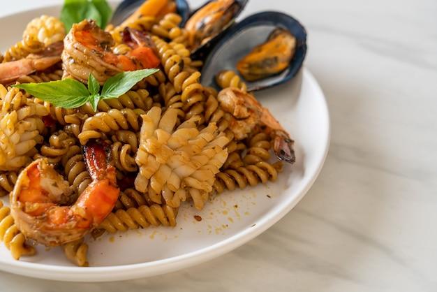 Обжаренные спиральные макароны с морепродуктами и соусом из базилика - стиль фьюжн