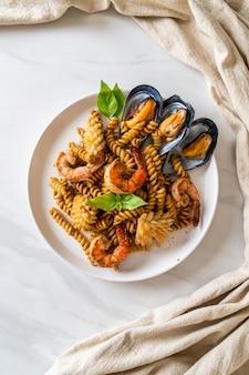 Жареная спиральная паста с морепродуктами и соусом из базилика - стиль фьюжн