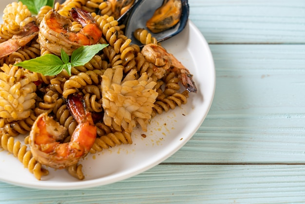 Stir-fried spiral pasta with seafood and basil sauce - fusion food style
