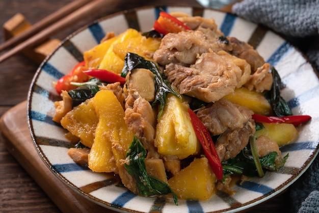 台湾のスリーカップチキンとパイナップルの炒め物。暗い木製のテーブルの表面に台湾の自家製のおいしい料理。