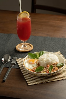 Жареный тайский базилик с фаршем из свинины, моркови и молодой кукурузы, с жареным яйцом и свежим базиликом, отсортированный в белом блюде на бамбуковой подставке, серой подставке для посуды, коричневом деревянном столе. копировать пространство