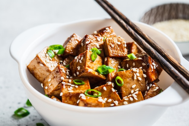 Stir fried tofu with sesame seeds and green onion in white bowl. vegan food concept.