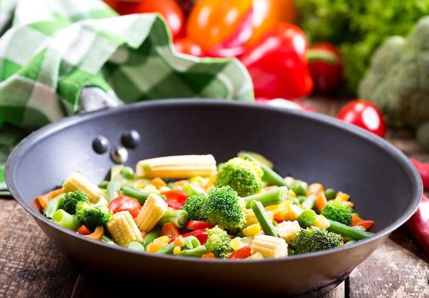 Перемешайте жареные овощи на сковороде на деревянном столе