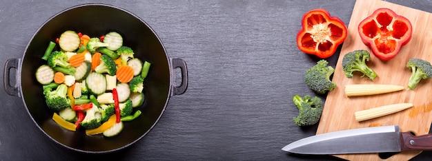 Stir fried vegetables in a wok on dark table, top view
