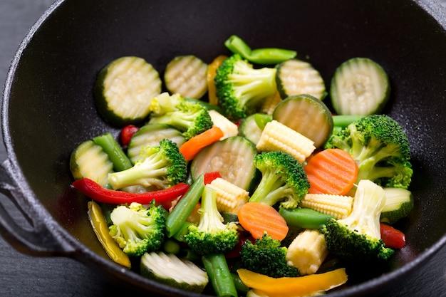 Stir fried vegetables in a wok on dark table
