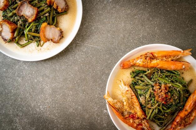 Жареная водяная мимоза с хрустящей свиной грудинкой и речными креветками на тарелке
