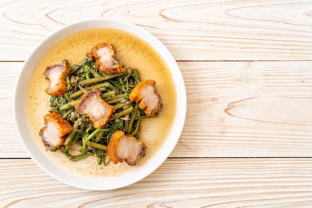 カリカリの豚バラ肉を皿に乗せたミズオジギソの炒め物