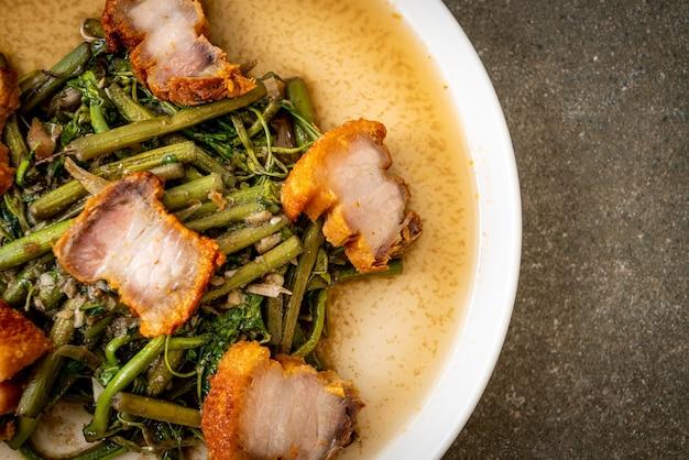 カリカリの豚バラ肉を皿にのせたミズオジギソの炒め物