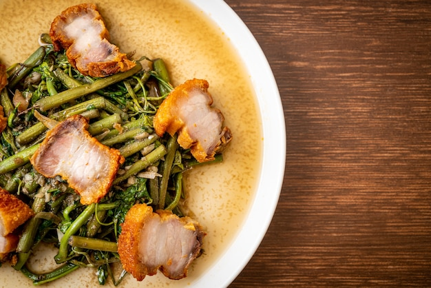 Stir-fried water mimosa with crispy pork belly on plate
