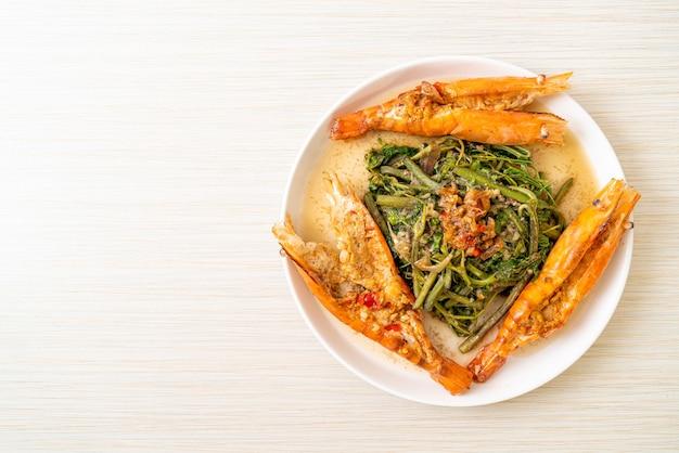Жареная водяная мимоза с речными креветками на тарелке