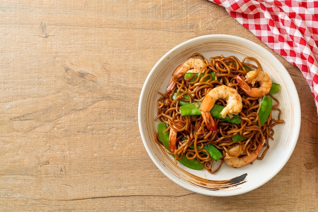 Stir-fried yakisoba noodles with green peas and shrimps - asian food style