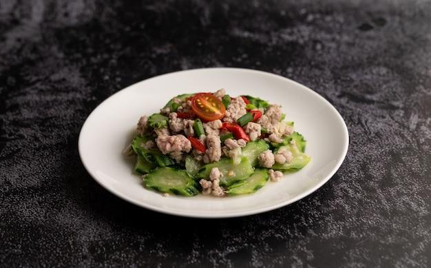 揚げたズッキーニと豚ひき肉を白い皿に入れて炒めます