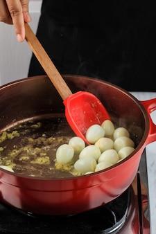 ゆで卵を赤へらで赤鍋に炒めます。ウズラの卵マヌー/韓国ジャンジョリムを作るキッチンでの調理プロセス