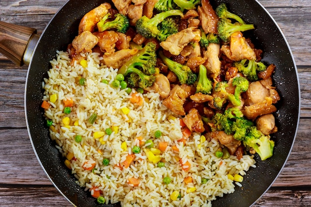 Stir-fry chicken and broccoli with rice in pan on wooden background. copy space.