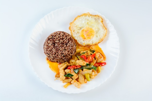 Stir fry chicken sweet onion and peppers, served with brown rice and fried egg on white plate