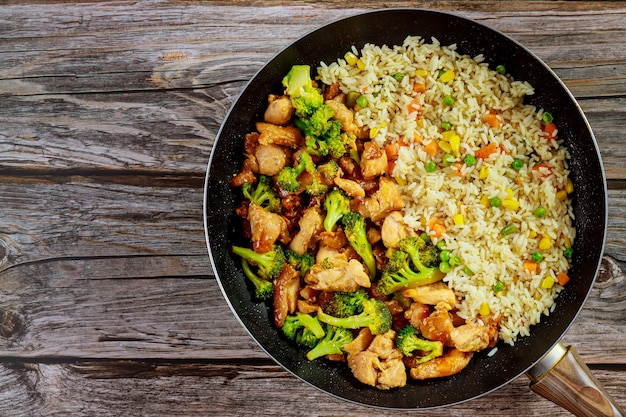Stir-fry chicken with broccoli in sweet and sour sauce and rice. asian meal.