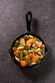 Stir fry chicken with vegetables on an iron pan