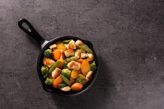 黒の背景に鉄鍋で野菜と鶏肉を炒めます
