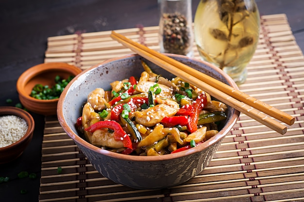 Stir fry chicken, zucchini, sweet peppers and green onion with chopsticks