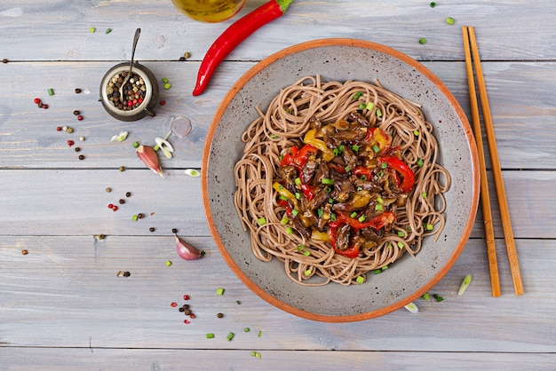 Stir fry from chicken hearts, paprika, onions and buckwheat noodles.