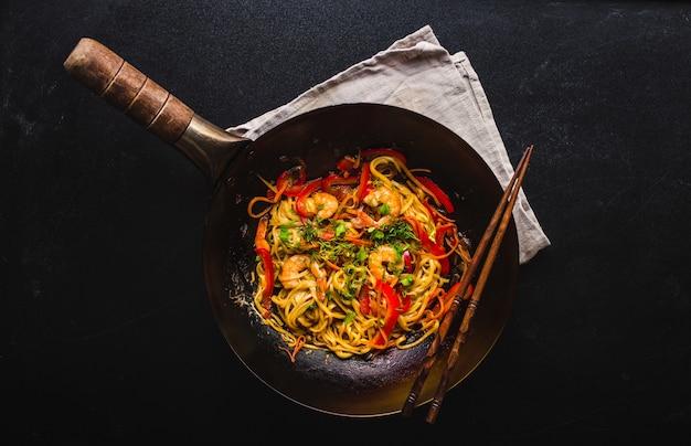 Stir fry noodles in traditional chinese wok, chopsticks. asian noodles with vegetables, shrimps.