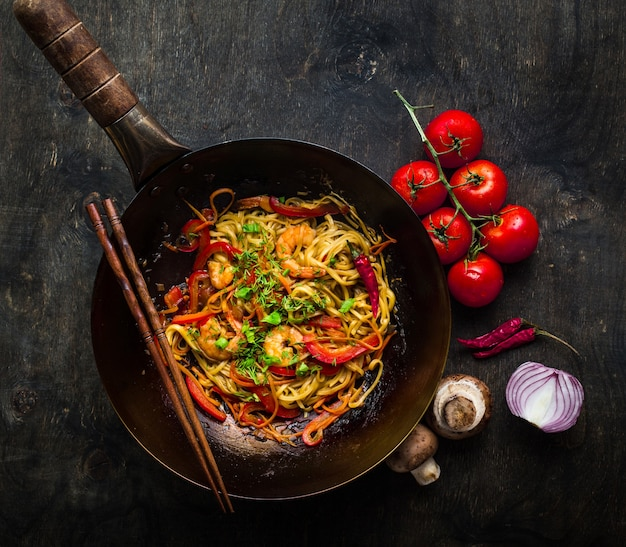 Stir fry noodles in traditional chinese wok, chopsticks. asian noodles with vegetables, shrimps.