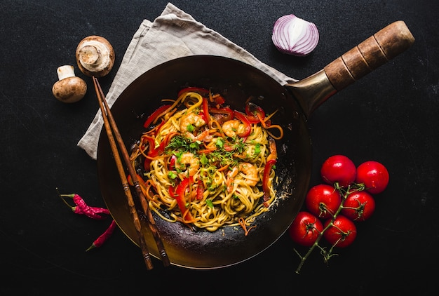 Stir fry noodles in traditional chinese wok, chopsticks. ingredients for cooking noodles.