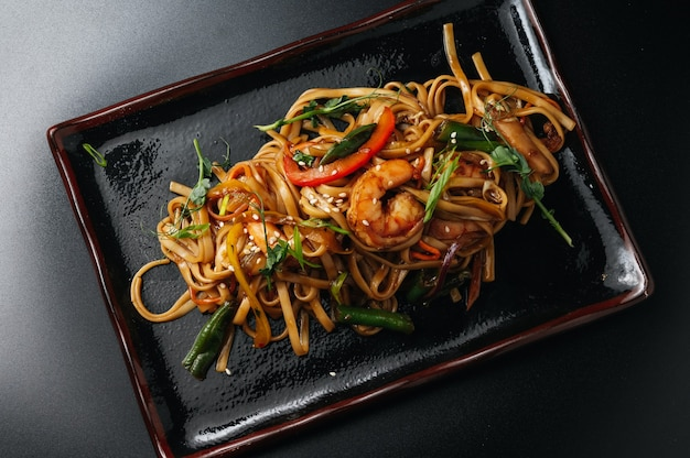 Stir fry noodles with vegetables and beef in black plate  black background close up