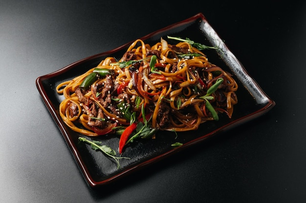 Stir fry noodles with vegetables and beef in black plate wooden background close up