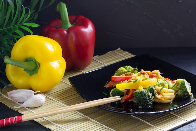 Stir fry noodles with vegetables on a black plate with soy sauce and ingredients on a bamboo mat
