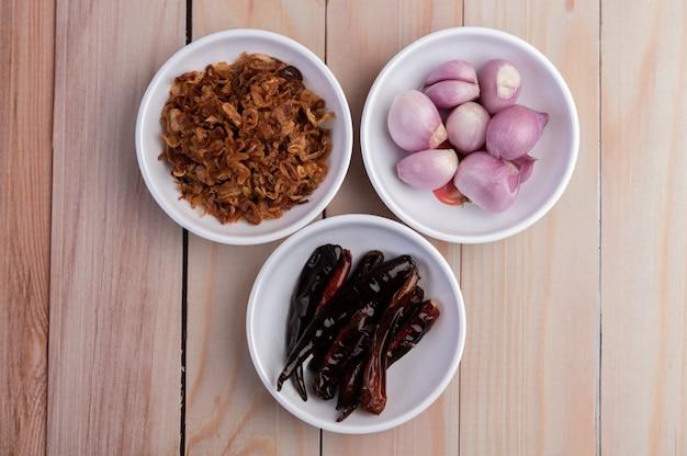 玉ねぎ、唐辛子、赤玉ねぎを木の床に白い皿に炒めます。