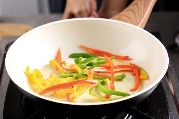 黒鍋でパプリカを炒め、キッチンで調理し、韓国のチャプチェ、中華牛の黒胡椒、イタリアのペペロナタなどのおいしい料理を作ります