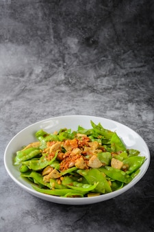 Stir fry snow peas with vietnamese grilled pork sausage, topping with crispy fried shallots and garlics