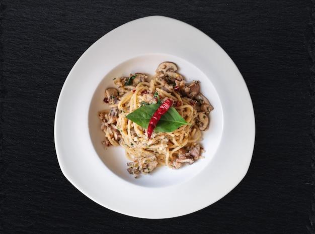 塩漬け魚、タイのスパイス、辛い唐辛子のスパゲッティを白い皿に炒めます