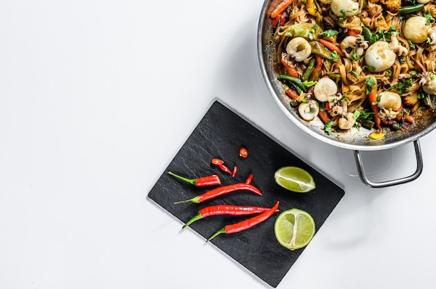 Stir fry udon noodles with seafood and vegetables. white background. top view. copy space