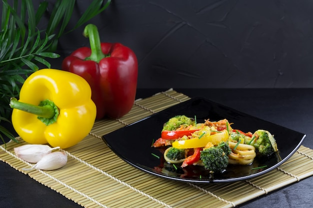 Stir fry udon noodles with vegetables on a black plate with ingredients on a bamboo mat
