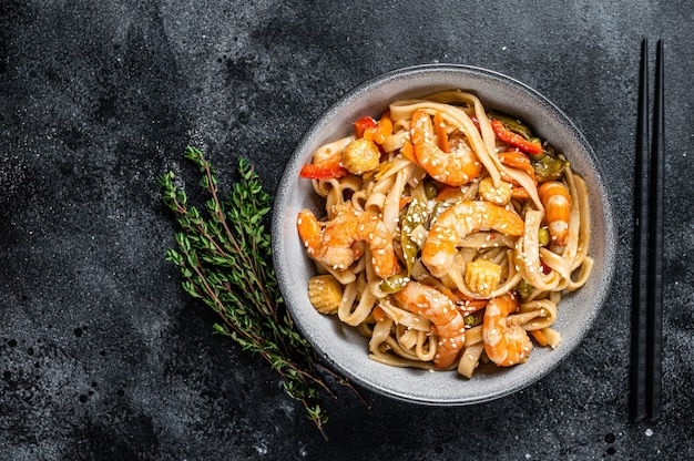 Stir-fry udon seafood noodles with shrimp prawns in a bowl. black background. top view. copy space.