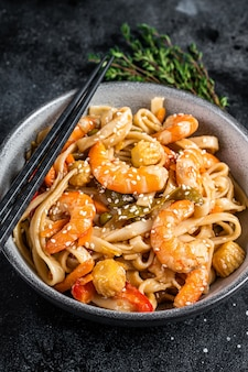 Stir-fry udon seafood noodles with shrimp prawns in a bowl. black background. top view.