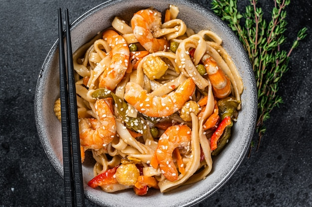 Stir-fry udon seafood noodles with shrimp prawns in a bowl. black