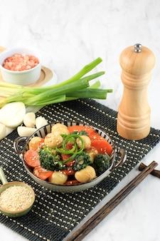 야채와 메추리알을 굴 소스에 볶습니다(telur puyuh saus tiram). 당근, 브로콜리, 삶은 메추라기 달걀로 만든 요리와 간장. 위에 참깨를 올려주세요