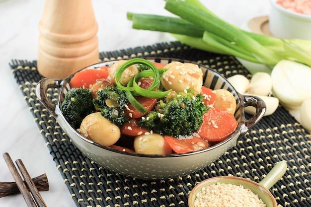 野菜とウズラの卵をオイスターソース(telur puyuh saus tiram)でかき混ぜ、その上にゴマの種を加えます