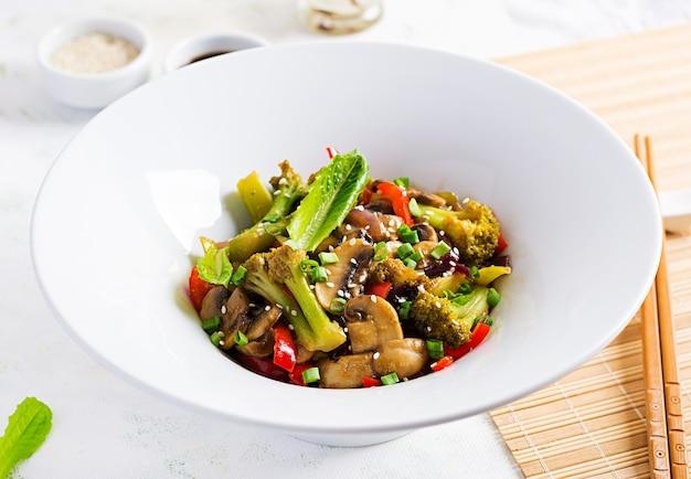 きのこ、パプリカ、赤玉ねぎ、ブロッコリーと一緒に野菜を炒めます。健康食品。アジア料理。