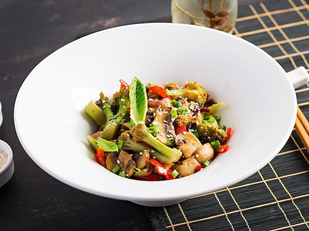 Обжарить овощи с грибами, болгарским перцем, красным луком и брокколи. здоровая пища. азиатская кухня.