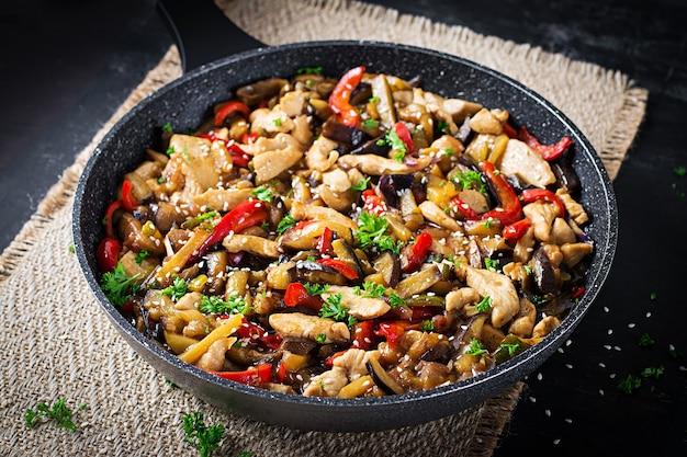 Жаркое движения с курицей, баклажанами, кабачками и сладким перцем - китайская еда.