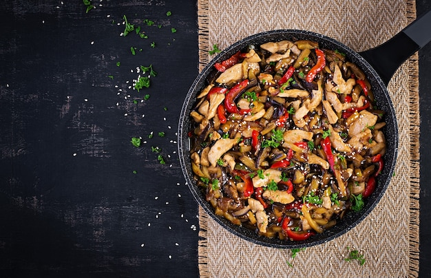 Stir fry with chicken, eggplant, zucchini and sweet peppers - chinese food. top view, above