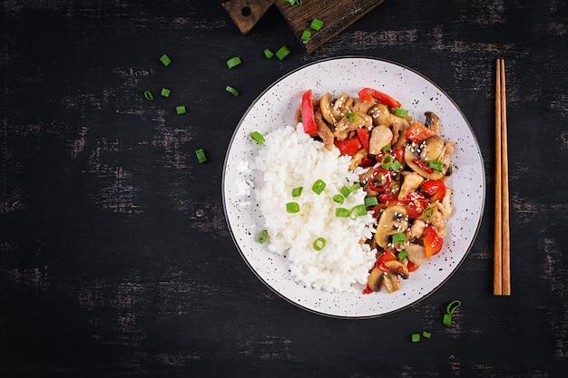 Жаркое движения с курицей, грибами, сладким перцем и отварным рисом. китайская еда. вид сверху, вверху