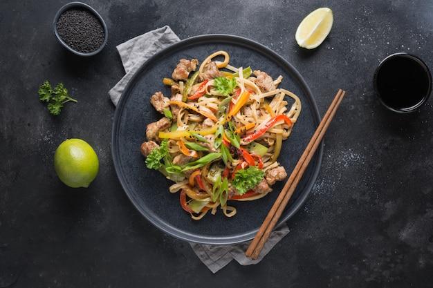 검은 돼지 고기와 야채를 곁들인 우동으로 볶습니다. 아시아 요리. 평면도.