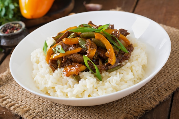 Stir frying beef with sweet peppers, green beans and rice