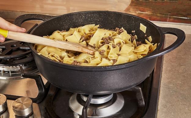 インターネットのレシピに従って、スパゲッティボロネーゼパンで揚げた牛ひき肉とスパゲッティを入れてかき混ぜます。
